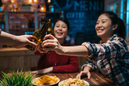Groep gelukkige vrienden die 's avonds laat bier drinken en roosteren in de brouwerijbar. Stockfoto