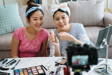 Giving review. Positive expressive young blogger creating make up video with friend sitting in living room on floor.