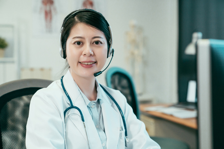 female doctor wearing headset while using computer at desk in clinic office.