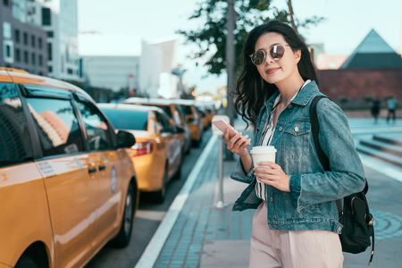 confident business woman using application of taxi service app on smart phone and holding coffee to go. 스톡 콘텐츠