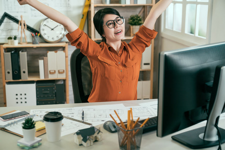 happy asian woman architect sitting at desk in modern office workplace stretching body after long day working on computer.