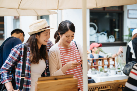 two asian women on vacation walking in outdoor creative market. girls friends shopping at vendor stand with wood pen smiling love like product. female travelers standing on street under umbrella.