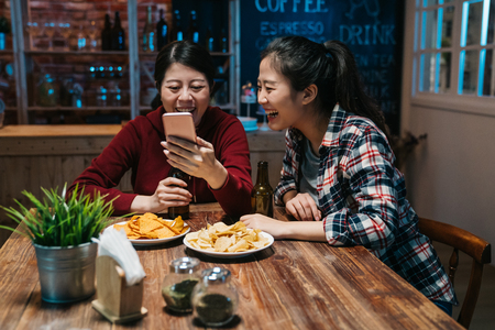 in bar single night party celebration in progress beautiful young people show mobile phone screen having great fun. two asian women best friends laughing browsing online social media drink beer pub.