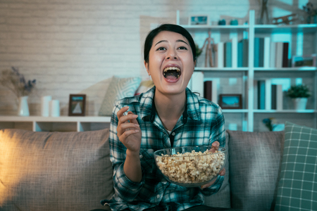 cheerful young asian woman with popcorn bowl sitting on sofa at night dark home. lady after work relax on couch laughing joy with open mouth wide watching tv movie funny comedy talk show program.