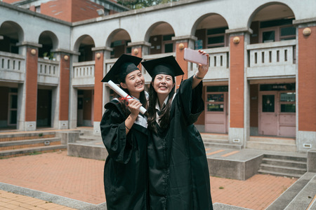 Graduation day group of asian female best friends smile for self portrait looking at smart phone. two young girls cheerful showing diploma taking selfie in traditional red brick building in campus.