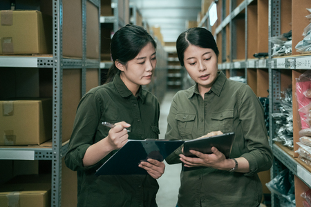 two asian woman warehouse worker with tablet and clipboard indoors. young girls employees in uniform discussing about goods amount. female staffs standing between cardboard box and products on shelf Stockfoto