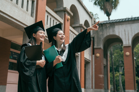 two young girls college students on graduation day holding textbook study abroad finish university. woman point finger showing friend smiling laughing talking chatting in traditional red brick house.