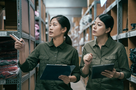 two asian young girl colleague in uniform walking together in factory warehouse. manager woman training new employee in storehouse. elegant ladies working in stockroom of famous clothes shop.