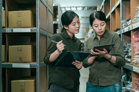 serious storehouse workers in uniform standing with colleague. teamwork partner working together with tablet and documents on clipboard writing. two girl coworker checking customer order in warehouse Stockfoto