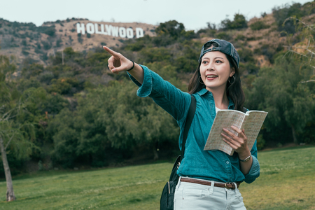 holidays and tourism concept. asian girl point looking for direction in nature mountain hill with hollywood sign in background surrounding by green forest trees . woman smiling holding guide book Reklamní fotografie