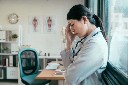asian woman doctor in despair misery sorrow leaning against window. upset unhappy young girl intern medical staff hand touching forehead deep thinking thoughtful. sad female nurse try solve problem Stockfoto - 124470401