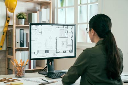 Vista posterior del arquitecto de la mujer asiática en camisa que mira en el proyecto del documento del modelo en línea de Internet del edificio verde. Trabajador de diseño de interiores femenino que trabaja en el monitor de la computadora de escritorio escribiendo teclado