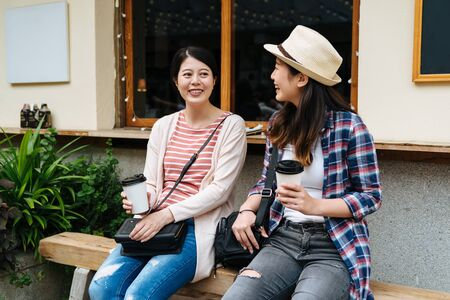 Two pretty girlfriends laughing while sitting in cafe bar outdoors.
