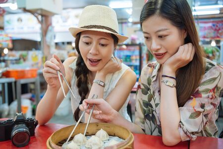 two beautiful japanese ladies tourists friends trying taiwanese local traditional food xiao long bao in bamboo steamer box.