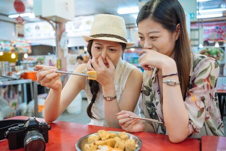 two young foreigner female travelers trying stinky tofu with chopsticks in local market.