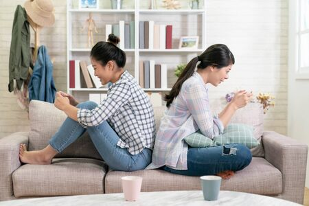 Cute young girl texting via social networks while friend sitting with back playing video games on cell phone.