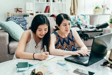 Lächelnde Freundinnen sitzen am Schreibtisch bei der Planung von Sommerferien. Standard-Bild