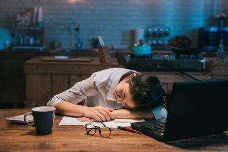 Sleepy exhausted asian woman employee working at wooden kitchen desk with laptop.