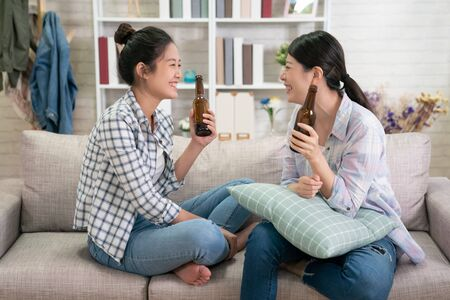 Group of young asian girl friends sitting on sofa and discussing something together with beer at home.