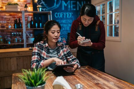 female customer ordering food at restaurant table seat in night bar holding touchpad. 免版税图像