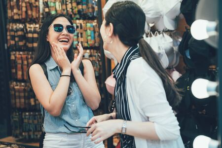Two lovely cheerful asian female friends try sunglasses while shopping together at clothing store. Beautiful women choose eyewear accessories shop laughing having fun with funny eyeglasses thailand