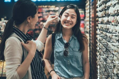 two pretty young asian female friends trying pair of earrings while shopping at jewelry store together. girl helping smiling sister choose accessories in fashion shop. happy women spend leisure time
