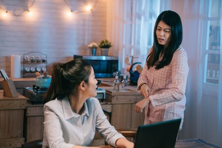 tired young girl in pink nightwear with hand gesture telling time on watch to her best friend hard working worker. female walking to home kitchen talking to business woman go to sleep early in night