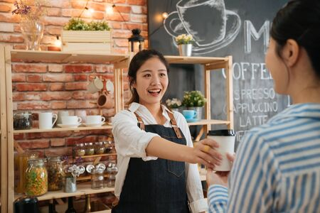 Beautiful friendly female barista giving coffee disposable cup to customer at counter of coffee shop. small startup business owner concept. office lady is regular client buy breakfast every morning Banque d'images - 125575237