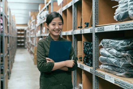 cute female worker holding clipboard in warehouse. young attractive girl staff standing in storehouse face camera smiling. happy woman stockroom employee surrounding by goods inventory in factory.