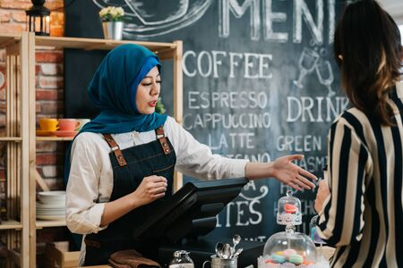 Young asian arabic waitress recommending businesswoman wear smart casual special course from counter in cafe bar. malay lady staff in coffee shop working talking to customer introduce hand gesture