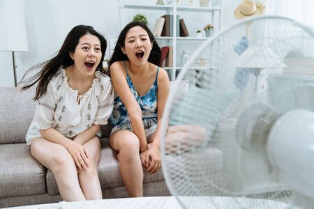 two cheerful women friends having fun with electric fan opening shouting yelling at it. playful young girls sitting on sofa with air cooler in front in living room with wide mouth funny face looking.