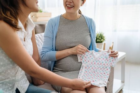 unrecognized two young asian happy smiling friends sitting on couch in living room chatting. elegant pregnant woman hold showing cute baby clothes. sister auntie sending gift to expecting child.