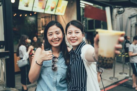 two pretty asian women tourist travel in taiwan taipei holding modern asian beverage bubble milk tea. girls showing face camera with tasty drink local specialty smiling with thumb up good on street