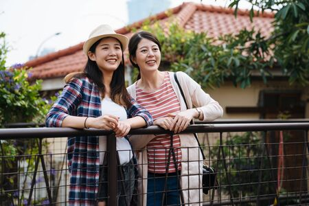German architecture ancient houses with red tile roofs in old town Germany Bavaria Rothenburg ob der Tauber. two asian young girls friends leaning on railing sightseeing curiously beautiful town view Stock fotó