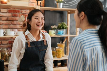 Young barista girl in apron and white shirt working at the counter in coffee shop. Nice smiling coffeehouse female staff taking order from customer in morning. businesswoman is regular client in cafe Banque d'images - 125943024