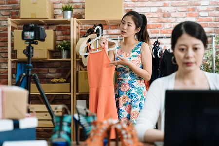 focus on beautiful asian woman  showing clothes to camera recording vlog video live streaming at online shop. small start up internet store on social media concept. female partner reply laptop