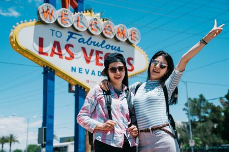 happy two cute young asian women travelers giving V signs as they stand arm in arm grinning at camera in urban on sunny summer day. sisters tourists taking picture with las vegas sign together 写真素材