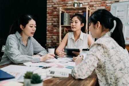 Attractive young businesswoman speaking to employees. elegant female business leader speaker talking at meeting in modern office. three girls teamwork partner of small startup business in discussion 스톡 콘텐츠