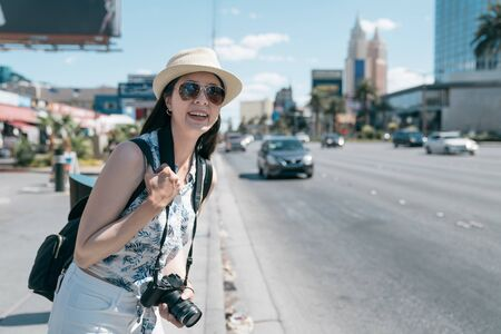 Smiling backpacker girl happy to spend free time walking city center on good warm sunny day. smiling female traveler with rucksack and camera waiting for public transport in las vegas strip road.