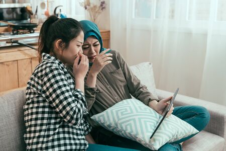 vintage style photo side view of two young asian girl friends sitting on couch with frowning face while watching thriller film on digital tablet. muslim woman in blue hijab traditional having fun. Standard-Bild