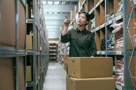 Warehouse worker woman collects cardboard boxes and parcels from shelf and puts them on cart. girl staff in green shirt point finger up while searching products in storehouse. manager stocktaking. Stockfoto