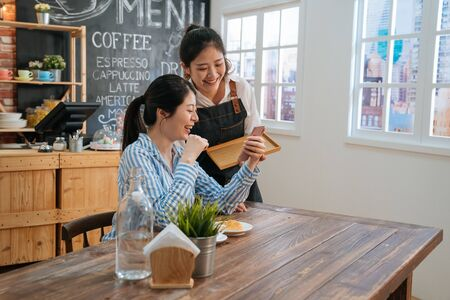 two female friends in coffee shop chatting and discussing on social media with mobile phone. waitress in apron served lady regular customer and gossip with her looking together on smartphone screen. 写真素材
