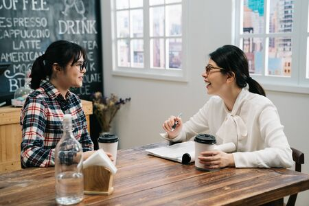 Friendly businesswoman interviewing new applicant candidate for marketing team staff in cafe store. elegant lady hr worker laughing holding coffee cup joyful good impression to job seeker girl.