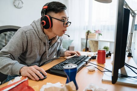 concentrated asian man with headset playing game on desktop at home. 写真素材