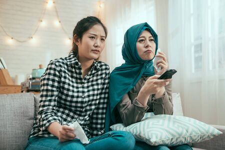 sad asian girl friends crying for touching movie on tv while sitting in comfort sofa in home.