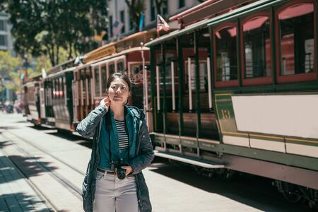 Cute smiling young woman on summer vacation walking on city street against cable car on street line in san francisco. Banco de Imagens