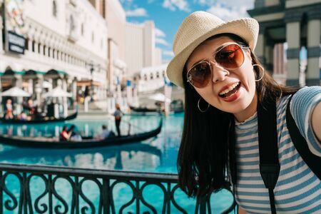 Traveler girl smiling at camera and make self photo with gondola on canal.