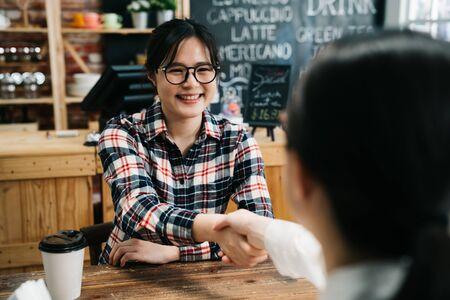 Smiling female candidate shaking hand with lady hr human resource manager in cafe bar. young girl joyful join new company got chance to work in dream office. success applicant job seeker coffee shop Foto de archivo