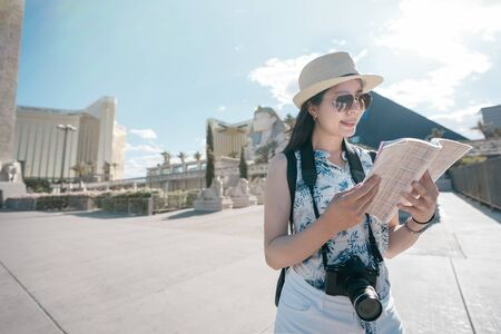 Sphinx and pyramid of Cheops in backgorund under blue sky. young female traveler visit resort and casino in Las Vegas Strip in Nevada United States. woman tourist holding guide book read information