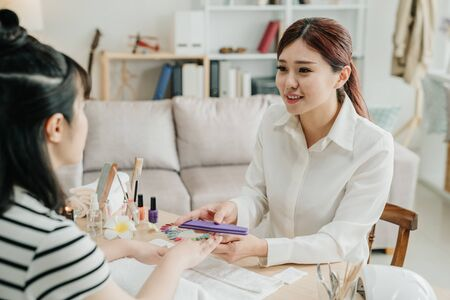 Manicure procedure in home service. beautiful manicurist smiling and looking at customer while using nail buffer on girl hands. confident beautician listening to client talking during work process Stock Photo